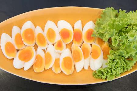amarillo y negro: huevos cocidos en un plato con lechuga.
