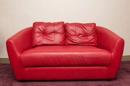 sofa: Red sofa in the room, white wall.
