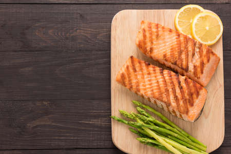 Grilled salmon and lemon, asparagus on the wooden background.