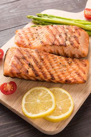 Salmon: Grilled salmon and lemon, asparagus, tomato on the wooden background. Stock Photo