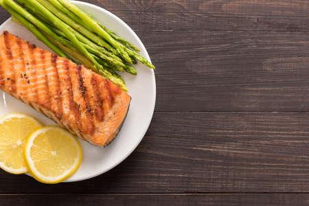 plato de pescado: Salmón a la plancha con limón, espárragos en el fondo de madera. Foto de archivo