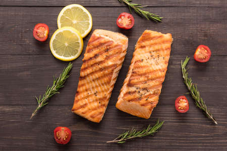 Grilled salmon and tomato, lemon, rosemary on the wooden background.