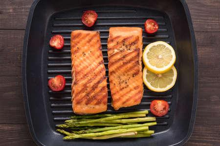 plato de pescado: Salmón a la parrilla cocinados barbacoa en una sartén sobre fondo de madera.