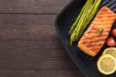 Grilled salmon cooked BBQ on a pan on wooden background.