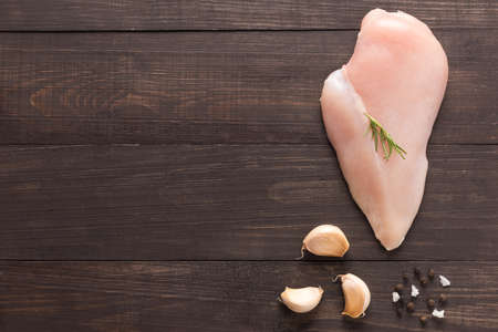 Top view raw chicken breast and garlic, pepper on wooden background. Stock Photo