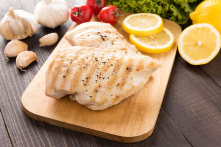 chicken breast: Marinated grilled chicken breasts on the wooden table. Stock Photo