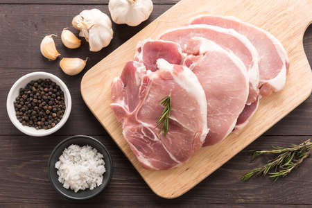 Top view raw fresh meat and salt, pepper, garlic on wooden background.