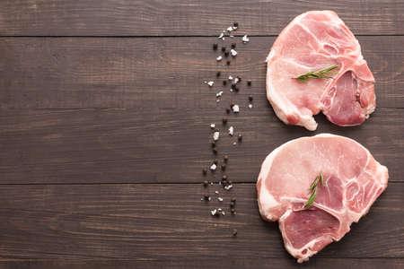 seasoning: Top view raw pork chop steak and salt, pepper on wooden background. Stock Photo