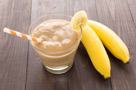 Banana smoothie and fresh banana on wooden background. Standard-Bild