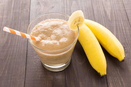 Banana smoothie and fresh banana on wooden background. Standard-Bild