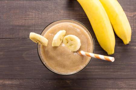 licuado de platano: Batido de plátano y plátano fresco en el fondo de madera. Vista superior.