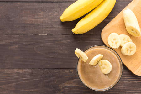 Banana smoothie on wooden background. Top view.