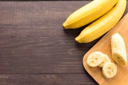 木製の背景にバナナ。平面図です。
