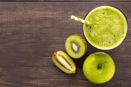 キウイと健康な緑のスムージー、素朴な木製の背景にリンゴ。 写真素材