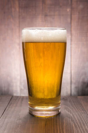 Glass of beer on the wooden background.