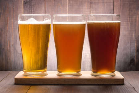 light to dark: Assortment of beer glasses on a wooden table.