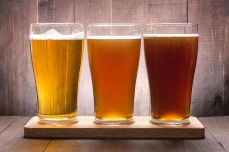 Sortiment pivní sklenice na dřevěném stole.