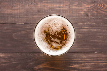 beer glass: glass of beer on a wooden background. Top view.