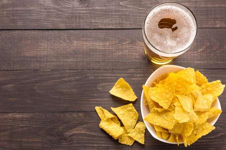 Glas bier met nachos chips op een houten achtergrond.