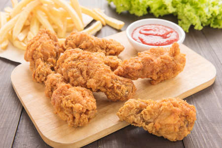 fried chicken drumstick and french fries on wooden table.