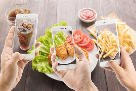 riends using smartphones to take photos of fried chicken and french fries and cola. Foto de archivo