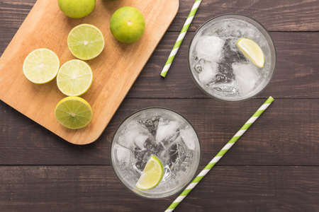 above view: Fresh cocktail with soda, lime on a wooden background.