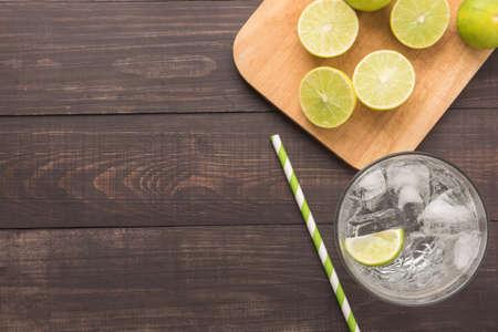 vaso con agua: Coctel fresco con soda, limón sobre un fondo de madera.