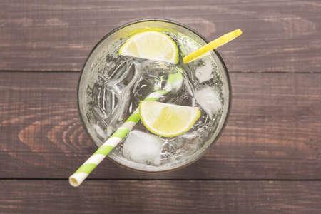 cocteles: Coctel fresco con soda, limón sobre un fondo de madera.