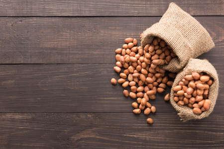 goober peas: Peanut in sacks on the wooden background.