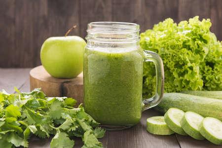 Gezonde groene groenten en groen fruit smoothie op rustieke houten tafel.