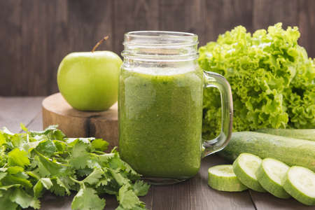 jugo verde: Verduras saludables y batido de fruta verde en mesa de madera rústica. Foto de archivo