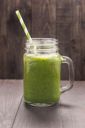 緑の野菜と素朴な木のテーブルに緑のフルーツのスムージー。