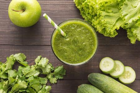 verduras verdes: Verduras saludables y batido de fruta verde en mesa de madera rústica. Foto de archivo