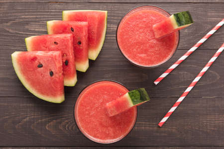 a straw: Healthy watermelon smoothie on a wood table.