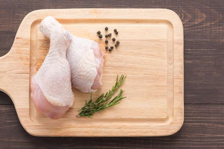 raw chicken: Raw chicken drumsticks on cutting board on wooden background.