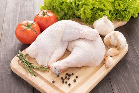 Ingrediënten en rauwe kip been op de snijplank op houten tafel. Stockfoto