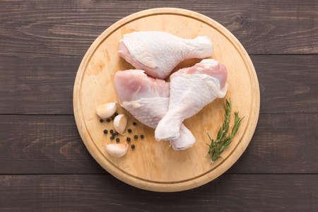 carne de pollo: Muslos de pollo crudo en la tabla de cortar en el fondo de madera.