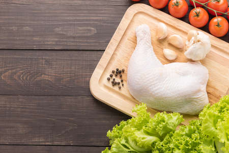 Ingredients and raw chicken leg on cutting board on wooden background.