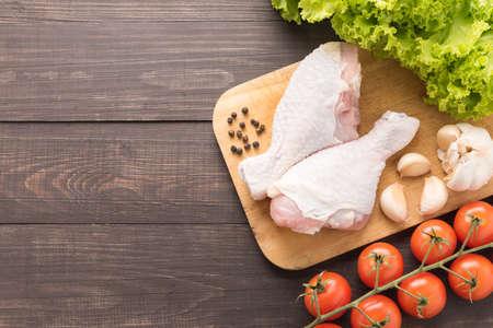 carne de pollo: Ingredientes y muslo de pollo crudo en la tabla de cortar en el fondo de madera. Foto de archivo