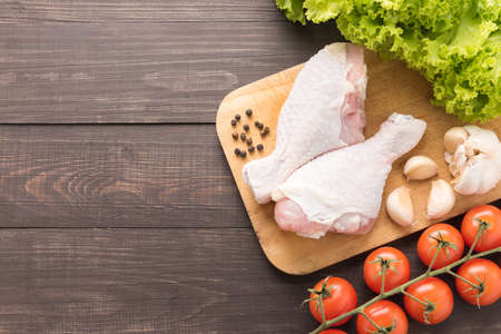 raw chicken: Ingredients and raw chicken leg on cutting board on wooden background.
