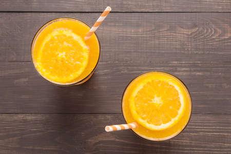 fruits juice: Fresh orange juice in glass on wooden background. Stock Photo
