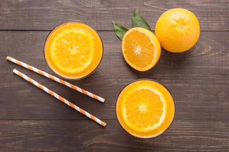 Fresh orange juice and oranges on wooden background.