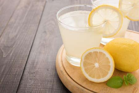 summer fruits: lemonade with fresh slice lemon on wooden table.