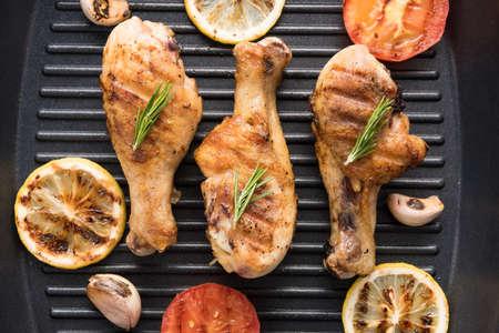 pollo a la brasa: Muslo de pollo asado y verduras en una sartén.