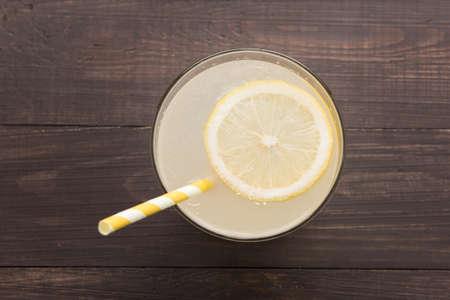 tropical drink: lemonade with fresh slice lemon on wooden background.
