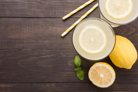 lemonade with fresh slice lemon on wooden background.