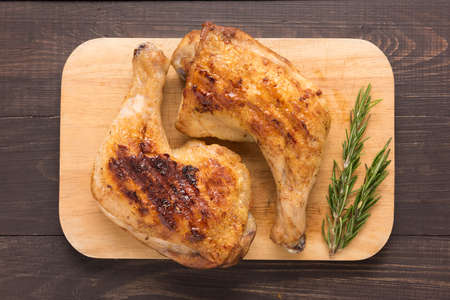 chickens: Grilled chicken lag and rosemary on wooden background. Stock Photo