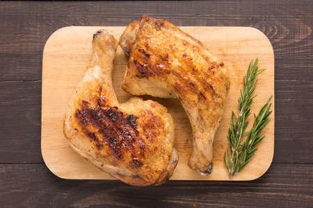pollo a la brasa: Lag pollo a la parrilla y el romero en el fondo de madera. Foto de archivo