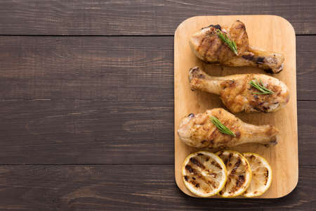 lemon: Grilled chicken drumstick and lemon on wooden background. Stock Photo