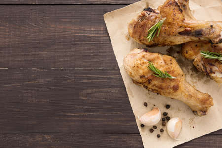 Grilled chicken drumstick and vegetable on wooden background.